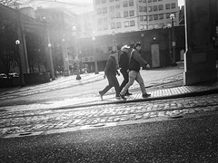 Walking In The Winter Sun (TMimages PDX) Tags: iphoneography photography image photo photograph streetscene fineartphotography geotagged people urban city street streetphotography portland pacificnorthwest sidewalk pedestrians buildings avenue road blackandwhite monochrome vignette