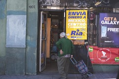 Enviando Su Amor (Bokehneer) Tags: usa california losangeles business door store signs ads spanish hunched abuelita latina elderly old woman