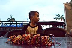 Bracelet Boy (Pedestrian Photographer) Tags: boy house june shirt truck t table restaurant evening shark cambodia riverside dusk hawk flag tshirt quay beggar sidewalk foo bracelets guest pm selling tee teeshirt beg hawker phnom hawking penh trinkets darken 2013 sihn dsc6595jpg dsc6595 sisowatch