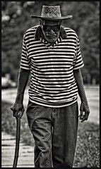 Man with a walking stick (Kevin Adams.1) Tags: old blackandwhite bw sunglasses cane walking beard stripes streetportrait oldman shades sidewalk jeans walkingstick strawhat grayhair