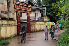 Yangon suburb (I.M.W.) Tags: yangon myanmar burma bicycle man women umbrella rainyseason canon550d canon dslr 28mm canonef28mm118 wet street asia people