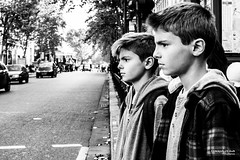 Street - Two boys, one look (Franois Escriva) Tags: street streetphotography candid people olympus omd paris france black white bw noir blanc nb photo rue boys expression look brothers sky sun light road trees cars hair face