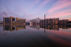 A Colourful Morning II (www.paulshearsphotography.com) Tags: 14second 1635mmf4 16mm 32bithdr 5dmarkiii boats buildings canarywharf canon5dmarkiii construction cranes dawn dirt dirty ef1635mmf4lisusm eos flats hdr iso100 millwalldocks outermillwalldocks paulshears paulshearsphotography pink redsky reflections sky smog smoggy sunrise trees water winter f11 wwwpaulshearsphotographycom