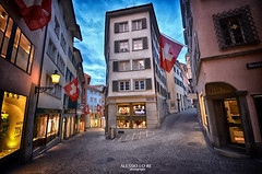Deep City (Alessio Lo Re) Tags: street door old light shadow sky cloud sun house color colour reflection window switzerland town colore cross pov flag zurich colourful tone hdr