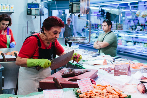 Market woman cutting up fish