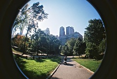 Central Park (timnutt) Tags: centralpark park buggy pushchair people tree buildings skyscrapers analogue film 35mm lomo lomography newyork nyc fisheye surreal