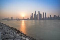 The Morning Sun (rishabdevbhaskar) Tags: sunrise rock rocks water reflection cityscape sun flare skyline dubai uae jumeirah jlt colors