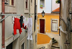 Upper Coimbra with facades and hanging laundry (Bn) Tags: coimbra historic river mondego alley street strolling cathedral glory churches roman university eaminium cultural serene monasteries neighbor upper town kings hills heritage exploring city romantic students sevelha old buildings beauty steep window tower universidadedecoimbra shadows holiday vacation laundry washing line clothes drying facades faades 50faves topf50 100faves topf100