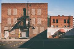 split face infill (simple pleasure) Tags: brickwall windows awning alley fireescape parkinglot shadows sky spokane