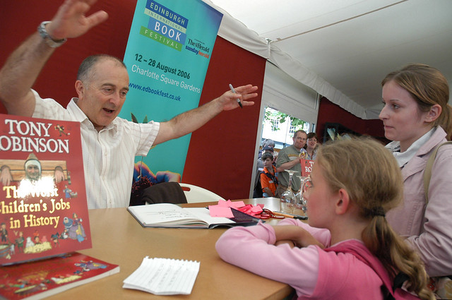 Tony Robinson signing books for young fans