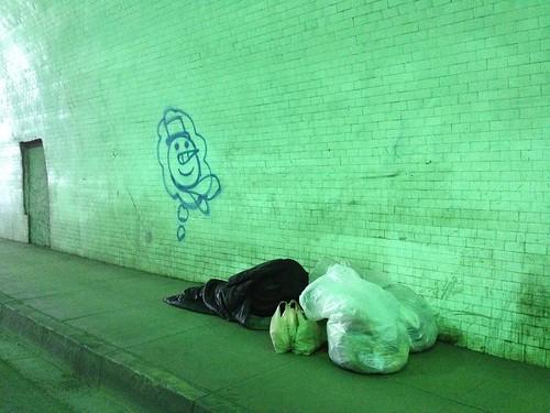 Homeless man sleeps adjacent Snowman themed graffiti in 2nd Street tunnel, Los Angeles