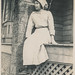 Young woman wearing a bonnet sitting on a porch