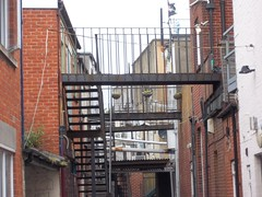 Behind Shops, Swanage, Dorset (doojohn701) Tags: gantry walkway metal stairs backstreets dorset swanage town uk pipes flag