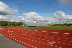 Track With Hurdle (sotrak33) Tags: athletics audience bleachers campus chain clouds cloudy college education fence field hurdle lanes link new race rochester running runningtrack school seats soccer spectators sports stands track york