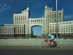Astana (Bendigoish) Tags: cycle man sun blue astana arch building