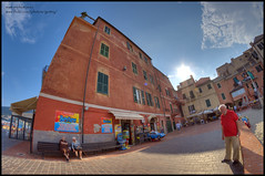 Laigueglia, Piazza Bastione (Gottry) Tags: travel sea sky people panorama sun holiday backlight square landscape mare cityscape outdoor liguria wide fisheye persone cielo piazza sole 8mm vacanza bastione controluce ligure d90 laigueglia samyang nikod gottry emanuelerinaldi wwwerphotoseu