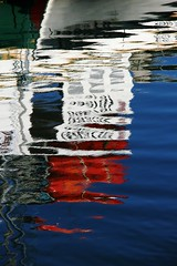 Watery Boat (Karen_Chappell) Tags: ocean blue red white canada abstract reflection water newfoundland boat marine harbour atlantic ripples colourful nfld eastcoast avalonpeninsula