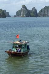 Fishing in Ha Long Bay (tmeallen) Tags: fishingboat traditionaldesign couple manandwoman turquoisewater unescoworldheritage limestonekarst islands clouds vietnameseflag halongbay northvietnam pullinginnets culture travel