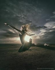 Beach Ballet (modulationmike) Tags: sunset backlit lighting flare dance jump coastal beach clouds moody atmospheric skirt sand contrast somerset
