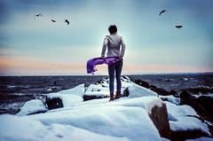 sea dream. (meg.reilly) Tags: ocean blue winter sunset sea portrait sky seagulls selfportrait snow motion cold texture ice water girl birds scarf self hair 50mm flying rocks aqua waves purple boots wind jetty coat atlantic boulders portraiture brunette vignette saltwater seafoam breakwater nikkor50