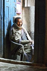 Man in doorway (Salle-Ann) Tags: nepal man night scarf doorway kathmandu traditionaldress elderlyman