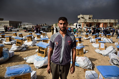 A man stands amidst relief kits being distributed by IOM for people displaced from Mosul, Iraq (DFID - UK Department for International Development) Tags: iraq iom internationalorganisationmigration mosul humanitarianaid ukaid shelter displacedpeople idps daesh humanitarianpreparedness camps idpcamps irak