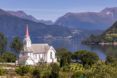 Dalsfjord church (NykO18) Tags: plants mountain art church water norway forest landscape woodwork woods flora europe faith cemetary religion peak hills manmade inlet fjord carvings mounds vestlandet mreogromsdal dalsfjorden voldsfjorden lauvstad naturalelement