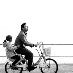 Riding in the milky way (Go-tea ) Tags: canon eos 100d street urban city qingdao huangdao asia asian china chinese people outside outdoor monochrome black white bw bnw blackwhite blackandwhithe man girl father daughter family together love bicycle bike sea side ride riding carried movement emotion basket young kid milkyway lines glasses coats fun activities care front back
