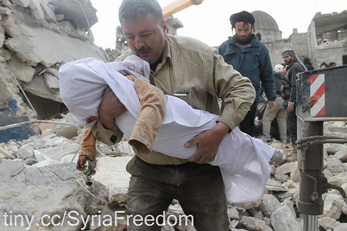 Syrian man carries the body of a victim out of the rubble of a destroy