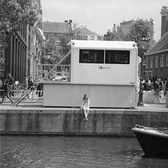 Police Cabin - with girl sitting on the waterside (PhotompNL) Tags: mf middenformaat medium format 6x6 vierkant square analogue bronica sqai schwarz weiss bw black white bianco nero blanc noir grain netherlands kodak zwartwit zw fekete feher anne frank huis politie amsterdam analoog bronicasqai camera film kodaktmax400120 nederland tmax 120 x6 mediumformat