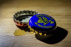 Hobgoblin (lacygentlywaftingcurtains) Tags: macromondays arrow hobgoblin beercaps beer spill tabletop indoor brewery shadows