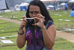 Taking a Picture (mikeeliza) Tags: camera portrait woman brown black hot girl beautiful grave graveyard yard canon dark hair asian glasses big eyes hands pretty arms skin shaped bare philippines fingers young almond curvy lips full pinay filipina brunette eyebrows busty pinoy mikeeliza