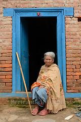 Bungamati (Bertrand de Camaret) Tags: door old blue nepal woman vertical asia seat femme ngc bleu stick porte asie chale baton nationalgeographic agee assit bertranddecamaret