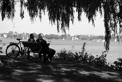 Couple on a bench (Ben Gun) Tags: old people bw white black tree bike lady river couple afternoon hamburg saturday mature fluss alster schwarz f40 weis nikond3000 sigma70300mmdgos