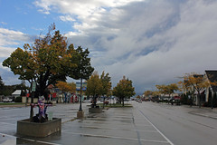 Wicked Weather at Mackinaw (Jan Nagalski) Tags: clouds storm stormclouds rain dark darkclouds blue bluesky hope wet wetpavement halloween halloweendecorations autumn autumncolor fallcolor trees dairyqueen pavement street city town perspective mackinawcity michigan jannagalski jannagal puddles rainpuddles reflections shops stores souvenirsstores restaurants weather
