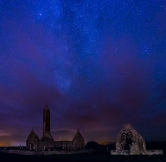 Starry Night at Kilmacduagh (TravLCox) Tags: pictures county city blue ireland sunset sky irish tower history galway beautiful abbey cemetery grave graveyard night clouds rural dark way stars dead photography death lights evening photo site scary ruins long exposure glow quiet republic cross buried dusk great picture folklore banshee haunted cathederal monastery galaxy round stunning legends cox travis historical ghosts aged celtic milky knots starry monastic settlement peacful gort kilmacduagh anitque tombtone thechallengefactory travlcox luncoln kilamacdaugh