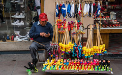 2016 - Mexico - San Luis Potosi - Calling my Supplier (Ted's photos - Returns late December) Tags: 2016 cropped mexico nikon nikond750 nikonfx sanluispotosi tedmcgrath tedsphotos tedsphotosmexico vignetting balloons shoes streetscene street people ballcap cellphone male man seating seated seat sitting moustache sanluispotosiphotos slp