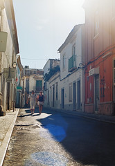 Romantic Getaway (joshuacolephoto) Tags: portugal portuguese street streetphotography streetwalk colour film 135 35mm nikon f100 nikonf100 sunny summer travel travelling journey road pavement couple people love lens flare lensflare blue
