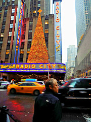Festive display on gloomy day (Robert S. Photography) Tags: street crossing pedestrian man rain rainyday radiocitymusichall christmastree marquee lights colors taxi cars city buildings midtown manhattan newyork holidays nikon coolpix l340 iso100 november 2016