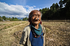 Apatani old woman in the ricefields of Ziro. Arunachal Pradesh, NE India (NeSlaB .) Tags: poverty old travel portrait woman india look canon nose photo women asia village traditional culture photojournalism tribal clothes ornaments tradition tribe society ricefields developingcountries reportage nationalgeographic ethnography ethnology neindia arunachalpradesh ziro ethnies apatani noseplugs neslab