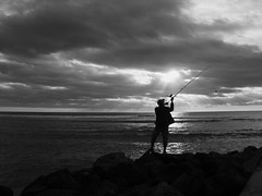 The Bait (Ren-s) Tags: sea mer fishing pêcher sun sunlight clouds soleil rayons nuages waves vagues fisherman pêcheur rocks pierre caillou shore sunset couchédesoleil noiretblanc blackandwhite laréunion reunionisland dom