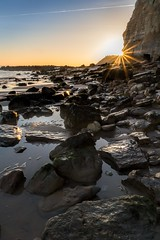 The dying sun (James Waghorn) Tags: sun beach sigma1750f28exdcoshsm pettlevel cliffs water reflections rocks contrails winter eastsussex d7100 sea light sunburst starburst england nd32