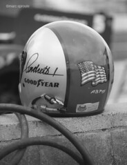 laguna seca march '87 (santa cruz graybeard) Tags: blackandwhite bw 1987 helmet americanflag racing autoracing goodyear motorsport lagunaseca indycar roadracing marioandretti blackwhitephotos newmanhaasracing openwheelracing mazdaracewaylagunaseca marcsproule