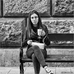 Don't panic, it's only my e-smoker... (John Riper) Tags: johnriper street photography straatfotografie square vierkant bw black white zwartwit mono monochrome hungary budapest candid john riper fujifilm fuji xt1 18135 young woman girl esmoker cafe latte macchiato watching eye contact glasses spectacles