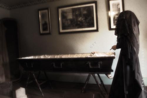 Woman mourns beside casket.