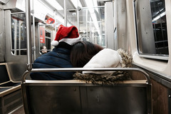 Santa & his sweetie ride the CTA (KevinIrvineChi) Tags: lovers amours amour amore amor love cta chicago chicagoist chicagotransit chicagotransitauthority santa santaclaus hat red white seats railroad rail railcar interior indoors inside ctabrownline night reflections reflection reflective passengers publictransit publictransport leaning nuzzling coats winter cold chiberia chilly jacket jackets steel shiny fluorescent sony dscrx100 elevated train l flickrvalentine couple