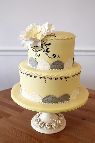 Yellow painted wedding cake scrollwork and flower