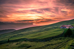 Across the red sky (marco soraperra) Tags: grass landscape sky sun sunset sunlight light shadow field green verde red orange colourful mountains switzerland suisse schweiz clouds nikon nikkor