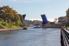 """Open Sesame"" (Jan Nagalski) Tags: bridge basculebridge drawbridge charlevoixbridge lakemichigan pineriver canal blue river autumncolor fallcolor trees colorfultrees harbor boat pleasureboat ferry ferryboat waterway charlevoix michigan jannagalski jannagal perspective curve railing heatherb beaverislander"