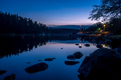 Dusk Harbour (Jens Haggren) Tags: olympus em1 dusk harbour sea water stones reflections sky bluehour colours trees boat jetty bridge lights clouds mood atmosphere nacka sweden jenshaggren